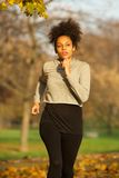 Young sporty woman running outdoors in the park. Portrait of a young sporty woman running outdoors in the park Royalty Free Stock Image