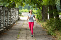 Young sporty woman running through the park in summer day. Royalty Free Stock Image