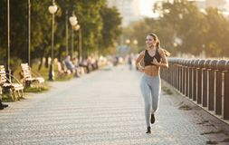 Young sporty woman running on quay in city park stock photos