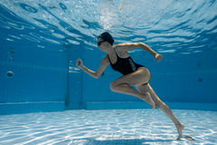 Young sporty woman running underwater. Stock Photo