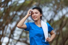 Young sporty woman running and wiping her sweat with a towel in. The park stock photography