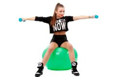 Young sporty woman sitting on fitball with dumbbells on white ba Royalty Free Stock Image