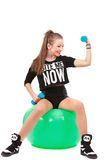 Young sporty woman sitting on fitball with dumbbells on white ba Stock Photo