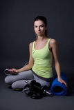 Young sporty woman sitting and listening music with phone over g Royalty Free Stock Image