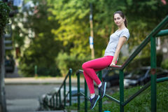 Young sporty woman sitting on the railing of the stairs in the alley in beautiful summer day Royalty Free Stock Images