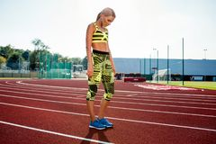 Young sporty woman sprinter athlete in sportswear resting after run on stadium track. Red treadmill in sport field Stock Images