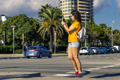 Young and sporty woman is standing next to the road and taking a picture of something. Sunny day. Orange t shirt and and bright sneakers. Barcelona, Spain Royalty Free Stock Photography