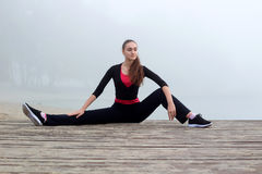 Young sporty woman stretches during fitness workout outdoor Stock Photo