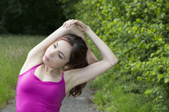 Young sporty woman stretching her arms outdoors Stock Photo
