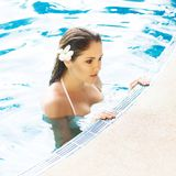 Young and sporty woman in swimsuit. Girl relaxing in a pool at summer. Royalty Free Stock Images