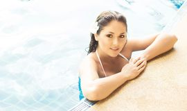 Young and sporty woman in swimsuit. Girl relaxing in a pool at summer. Resort concept Royalty Free Stock Image
