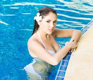 Young and sporty woman in swimsuit. Girl relaxing in a pool at summer. Resort concept Royalty Free Stock Photo