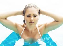 Young and sporty woman in swimsuit. Girl relaxing in a pool at summer. royalty free stock image