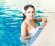 Young and sporty woman in swimsuit. Girl relaxing in a pool at summer. Royalty Free Stock Photography