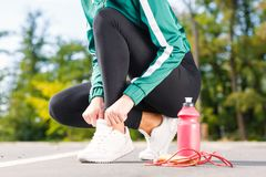 A young sporty woman ties up shoelaces on sneakers. A girl with perfect body doing exercises. Stock Photo