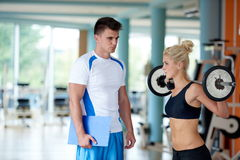 Young sporty woman with trainer exercise weights lifting Royalty Free Stock Photography