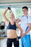 Young sporty woman with trainer exercise weights lifting Royalty Free Stock Photo