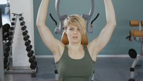 Young sporty woman on training apparatus in the gym. Young woman wearing sporty outfit is in the gym. Sporty young woman sits at the training apparatus. Woman stock footage