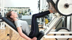 Young sporty woman training legs in gym. Athletic woman training her quads at machine press at gym. People, fitness and bodybuilding stock video
