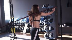 Young sporty woman is training muscles of hands and back using rubber tapes. She is tensing muscles, standing back to stock video