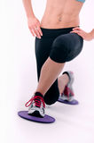 Young sporty woman using glide disks. Young sporty woman in the gym centre using glide disks Royalty Free Stock Photo