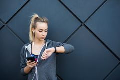 Young sporty woman using smart watch, standing at black graffiti wall background, copy space. Modern technology and fitness concep. Young sporty woman using stock image