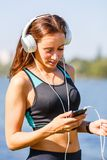 Young sporty woman using smartphone on training Royalty Free Stock Photo