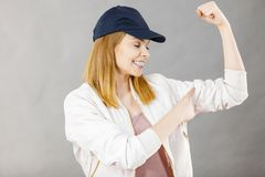 Young woman showing her arm muscles. Young sporty woman wearing cap and sportswear showing her arm muscles enjoying workout results. Studio shot on grey stock images