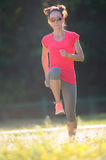Young sporty woman wearing colorful sportswear running  and doin Stock Image