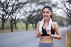 Young sporty woman with white towel resting after workout sport. Exercises outdoors at the park Stock Photos