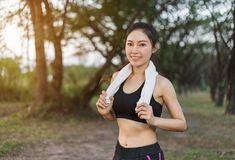 Young sporty woman with white towel resting after workout sport. Exercises outdoors at the park Royalty Free Stock Photo