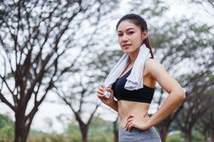Young sporty woman with white towel resting after workout sport. Exercises outdoors at the park Royalty Free Stock Photography