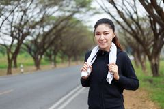 Young sporty woman with white towel resting after workout sport. Exercises outdoors at the park Stock Photo
