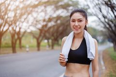 Young sporty woman with white towel resting after workout sport. Exercises outdoors at the park Royalty Free Stock Images