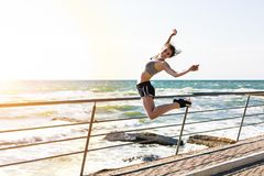 Woman working out at the beach. Young sporty woman working out at the beach Stock Image