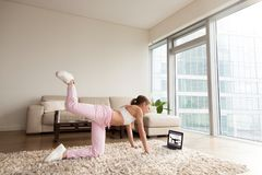 Young sporty woman working out at home, online fitness training. Young sporty woman working out at home, teenager doing fitness exercises on living room floor Stock Image