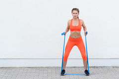 Young sporty woman working out with latex bands royalty free stock photography