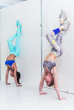 Young sporty women doing handstand exercise. Athletic girls standing in advanced downward-facing tree pose leaning Royalty Free Stock Photography