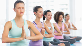 Young sporty women with joined hands sitting in row Royalty Free Stock Photos