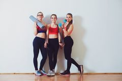 Young sporty women after training in fitness studio. Fitness, sport and healthy lifestyle concept. Group of females in sportswear royalty free stock photo