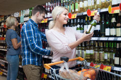Young spouse buys wine in the store. Man and blonde women buying wine in the store Stock Photography