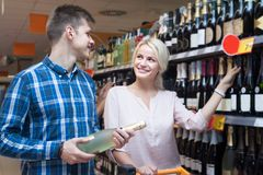 Young spouse buys wine in the store. Young positive spouse buys wine in the store Stock Image
