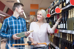 Young spouse buys wine in the store. Young smiling spouse buys wine in the store Royalty Free Stock Photo