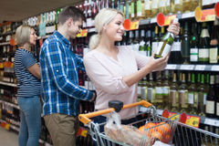 Young spouse buys wine in the store. Young smilinge couple buys wine in the store Royalty Free Stock Photo
