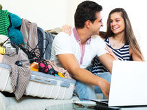 Young spouses browsing web and packing luggage Stock Images