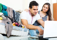 Young spouses browsing web and packing luggage Stock Photo