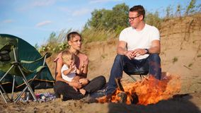 A young family with a child sitting near a campfire in nature in the summer, near a tent stock video