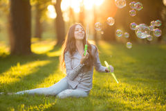 Young spring fashion casual woman blow bubbles in the sunset in Stock Image