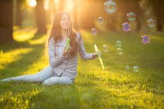 Young spring fashion casual woman blow bubbles in the sunset in Royalty Free Stock Photography