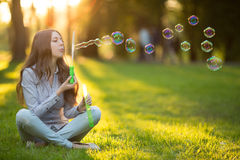 Young spring fashion casual woman blow bubbles in the sunset in Royalty Free Stock Photo